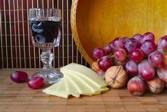 Vinho, uvas e queijo em uma placa Foto de Stock Royalty Free
