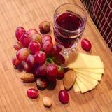 Vinho, uvas e queijo na placa Fotos de Stock Royalty Free