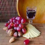 Vinho, uvas e queijo na placa Imagens de Stock