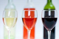 Vinho vermelho, branco e cor-de-rosa nos vidros com frascos atrás Imagens de Stock