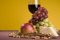 Vinho vermelho com uva, maçã e queijo em uma placa. Imagem de Stock