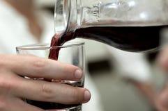 Vinho vermelho de derramamento Imagens de Stock