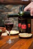 Vinho vermelho de derramamento imagem de stock
