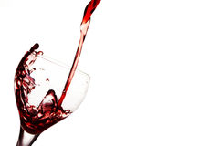 Vinho vermelho de derramamento no vidro Fotografia de Stock