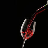 Vinho vermelho de derramamento no vidro de vinho Imagens de Stock Royalty Free