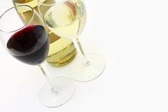 Vinho vermelho e branco em dois vidros com um frasco Foto de Stock Royalty Free