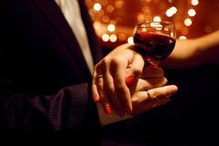 Vinho vermelho e mãos dos amantes fotos de stock