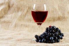 Vinho vermelho e uvas no fundo do vintage Fotos de Stock