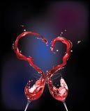Vinho vermelho que derrama e que dá forma à forma do coração Fotografia de Stock Royalty Free