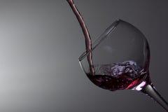 Vinho vermelho que derrama no vidro foto de stock royalty free
