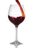 Vinho vermelho que derrama no vidro Imagens de Stock
