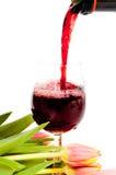 Vinho vermelho que derrama no vidro de vinho foto de stock