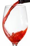 Vinho vermelho que derrama no vidro de vinho de um bottl do vinho Imagem de Stock Royalty Free