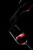 Vinho vermelho que derrama no vidro de vinho no preto Fotos de Stock Royalty Free