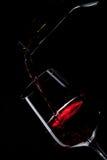 Vinho vermelho que derrama no vidro de vinho no preto Foto de Stock