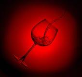 Vinho vermelho que está sendo derramado no vidro Fotografia de Stock