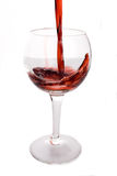 Vinho vermelho que está sendo derramado em um vidro de vinho Imagens de Stock