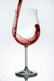 Vinho vermelho que está sendo derramado em um vidro de vinho Fotografia de Stock Royalty Free