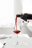 Vinho Vinho tinto de derramamento da garrafa no vidro de vinho bebidas Fotos de Stock