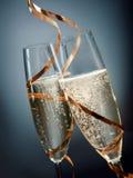 Vinhos em vidros de flauta com projeto dos laços do ouro Fotografia de Stock