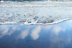 Vinka att svepa på kusten och molnen reflekterade i våt sand royaltyfri fotografi