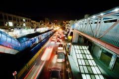 Vinka ljus av att rusa bilar på den ljusa gatan av nattstaden Arkivbild