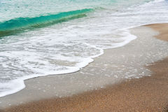 Vinka med skum på stranden, sandig strand Royaltyfria Bilder
