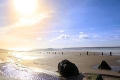 Vinka säkerhetsbrytare på solnedgången på en guld- stenig strand Arkivfoton