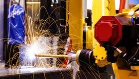Vinka svetsningrobotar i fabriken med gnistor, tillverkning, bransch, fabrik royaltyfria bilder