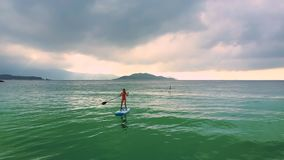 Vinka till flickaanseendet på paddleboard bland havet arkivfilmer