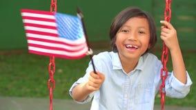 Vinkande amerikanska flaggan för flicka, medan le arkivfilmer