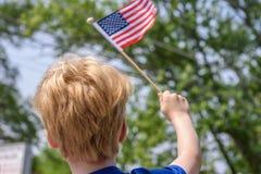 Vinkande amerikanska flaggan för pojke Royaltyfri Foto