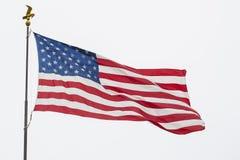 Vinkande amerikanska flaggan och Eagle Pole som isoleras Arkivfoton
