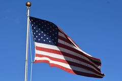 Vinkande amerikanska flaggan på en Pole royaltyfri bild
