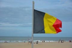 Vinkande belgisk flagga på havet Arkivfoto