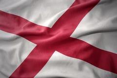 Vinkande färgrik flagga av den alabama staten Royaltyfria Bilder