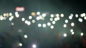 Vinkande ficklampor för folkmassa under en musikhändelse arkivfilmer