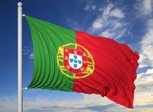 Vinkande flagga av Portugal på flaggstång Royaltyfri Bild