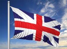 Vinkande flagga av UK på flaggstång Royaltyfri Foto