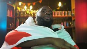 vinkande flagga för Afro--amerikan fan av England i stången, rubbning om nederlag för sportlag arkivfilmer