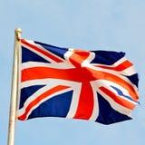 vinkande flagga i färgen och vågen för blå e-himmel den brittiska Arkivfoto