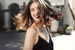 Vinkande hår för lycklig stilfull kvinna i solljus på den gamla europeiska staden royaltyfri foto