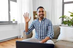 Vinkande hand för indisk manlig blogger hemma arkivfoton