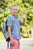 Vinkande hand för lyckligt skolbarn i universitetsområde Royaltyfri Fotografi