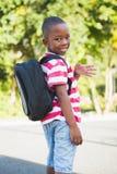 Vinkande hand för lyckligt skolbarn i universitetsområde Royaltyfri Foto