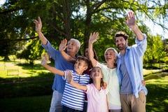 Vinkande hand för mång- utvecklingsfamilj i luft på parkera Royaltyfri Foto
