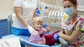 Vinkande hand för nätt patient, medan sitta på den tand- fåtöljen bredvid orthodontist i rubber handskar och medicinsk maskering  lager videofilmer