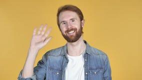 Vinkande hand för rödhårig manman till välkomnandet, gul bakgrund stock video