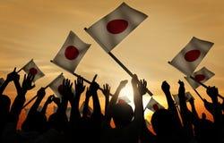 Vinkande japanflaggor för grupp människor i tillbaka Lit Arkivbild