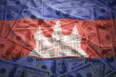 Vinkande kambodjansk flagga på en amerikansk dollarpengarbakgrund Royaltyfri Bild